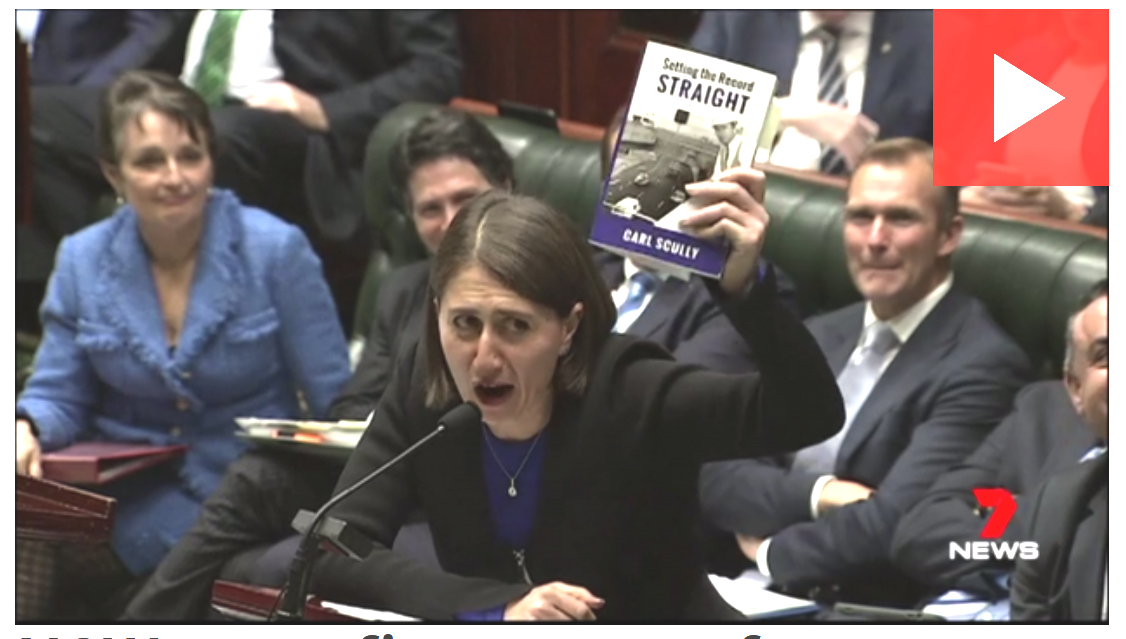 Gladys Berejiklian holding Carl Scully's book in Parliament